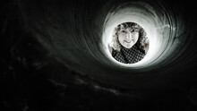 Close-up Portrait Of Woman Looking Through Concrete Pipe