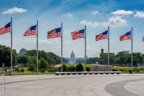 American flags at sunny day and Capitol Building in background in Washington DC, USA.