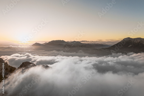 Fotografie, Tablou Aerial view above the cliffs and mountains meeting the sky and clouds