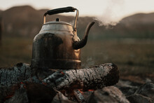 Close Up Old Kettle Heated On A Bonfire On A Green Mountain Meadow. Epic Travel In The Mountains.