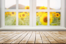 Empty Wooden Desk With White Window Against Blured Beautiful Sunflower Field With Sunlight