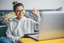 Millennial Woman Having Video Call On Her Computer At Home. Smiling Girl Studying Online With Teacher.