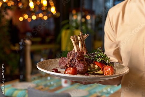 Canvas Hands holding cooked Tomahawk long bone ribeye steak on a serving board