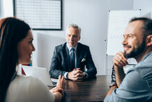 Mature Investor Looking At Smiling Businesspeople Talking On Blurred Foreground In Office