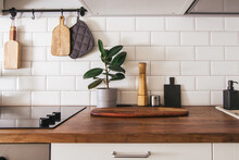 Kitchen Brass Utensils, Chef Accessories. Hanging Kitchen With White Tiles Wall And Wood Tabletop.Green Plant On Kitchen Background