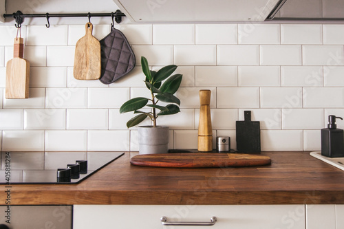 Fototapeta Kitchen brass utensils, chef accessories. Hanging kitchen with white tiles wall and wood tabletop.Green plant on kitchen background obraz