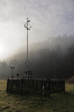 Small Weather Station On Field Among A Foggy Forest.