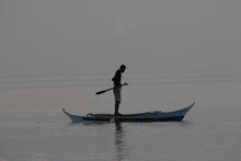 Silhouette Man Standing In Boat On Sea Against Sky