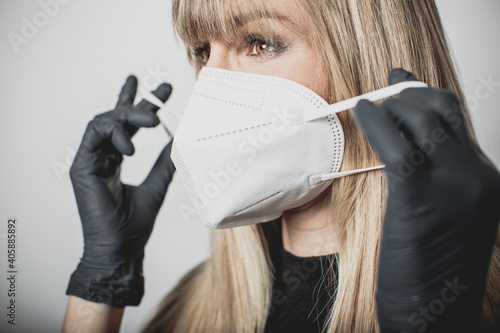 young, blond beautiful woman puts ffp2 protective mask on with protective medical gloves for protection against corona