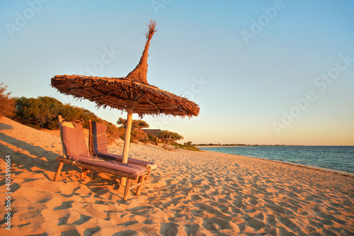 Papel de parede Two empty wooden sunbeds facing the sunset, sea in background, straw sun shade a