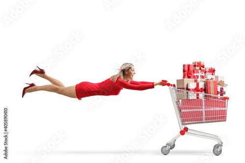 Attractive woman in a red dress flying with a shopping cart full of presents Fototapete