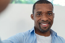 Portrait Of African American Handsome Man Smiling Friendly Aking Selfie Of Himself In Their Living Room At Home. People Man Lifestyle Concept.
