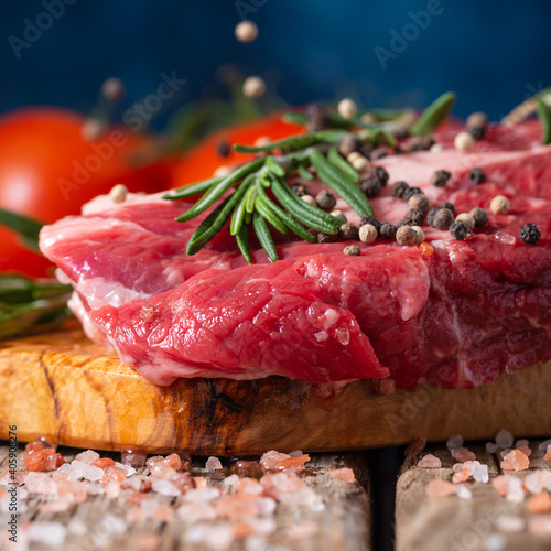 Foto Raw beef meat with spices, tomatoes and rosemary on wooden cutting board o blue background