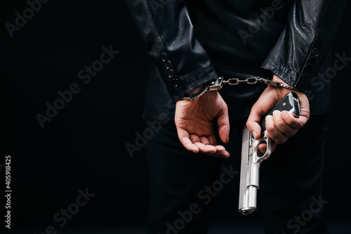 Back view of gangster holding real gun in hands and arrested in handcuffs Fototapet