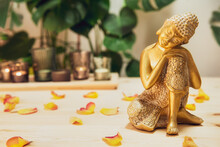 Golden Bronze Buddha Decorative Statuette With Flower Petals On Wooden Table With Burnig Candles, Monstera Plant Background. Meditation Ritual, Spirituality, Buddhism And Religion. Selective Focus