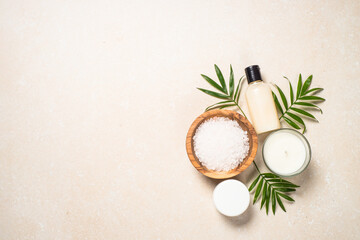 Fototapeta na wymiar Spa background. Spa product composition with palm leaves, cosmetic and sea salt at stone table. Flat lay image.