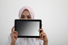 Portrait Of Woman With Hijab Holding Digita Tablet Against White Background