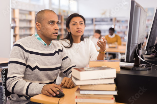 Valokuva Interested latin american man studying in computer class in public library