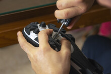 Closeup Shot Of A Male Assembling His Cycling Carbon Road Shoes And Attaching Cleats For Pedals
