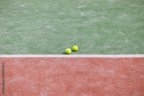 Fototapeta Closeup shot of the green-red tennis court with two tennis balls - a healthy lif