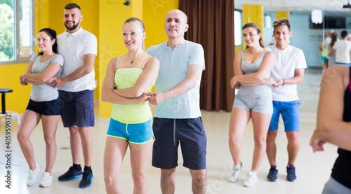 Leinwand Poster Emotional men and women dancing salsa in dance hall