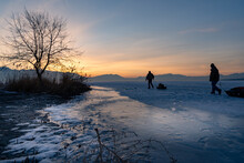 Ice Fishermen Trudge Across A Frozen Lake At Sunrise - Silhouette Pulling Equipment On Sleds