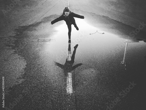 Fotografie, Obraz Girl Standing With Arms Outstretched On Water Puddle