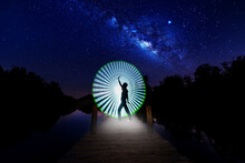 Digital Composite Image Of Man Dancing Against Light Painting On Pier By Lake At Night