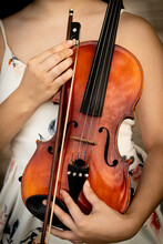 Vertical Closeup Of A Female Holding A Violin