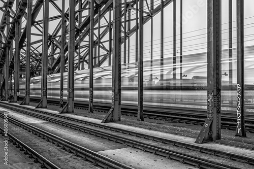 Fototapeta Grayscale shot of a railway and a train movingin long exposure