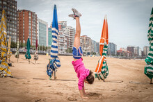 Girl Doing Handstand On Beach Against Buildings In City
