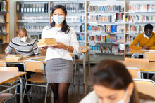 Young Adult Woman In Protective Face Mask Working With Books, Finding Information At Library
