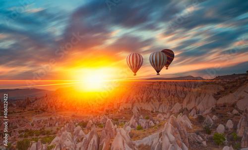 Leinwand Poster Hot air balloon flying over rock landscape at Cappadocia - Goreme, Turkey
