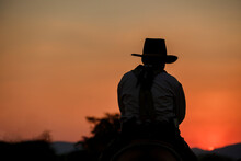 Silhouette Image Of Cowboys Riding On Horseback At Sunset