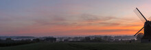 Panorama View Of View Of English Countryside On A Misty Morning At Dawn With Partial View Of Windmill
