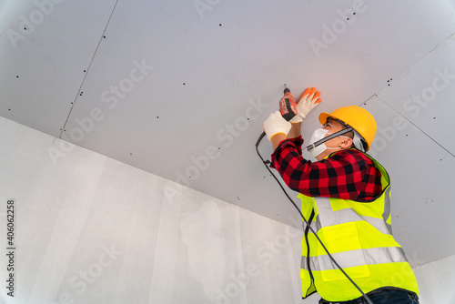 Fototapeta Asian construction worker used electric drill installation ceiling