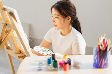 Young Girl Sitting On The Floor Learning To Draw By Herself