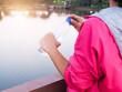 Leinwandbild Motiv Midsection Of Woman Holding Water Bottle By Lake