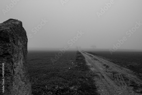 Dirt Road On Field Against Sky During Foggy Weather