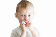 A Little Boy Of Three Years Old Eats Strawberries On A White Background.