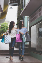Beautiful Woman Holding Shopping Bags With Friend Walking Amidst Building