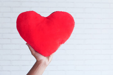 hand holding red heart symbol on white background