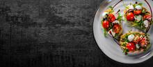 Italian Bruschetta With Roasted Tomatoes, Mozzarella Cheese, Balsamic Vinegar And Herbs On Plate On Dark Grey Black Slate Background