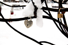 Heart Shaped Padlock On A Wrought Iron Railing Of A Bridge On A Winter Day