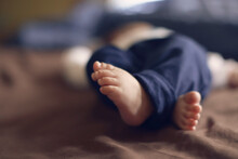 Low Section Of Baby Boy Lying On Bed
