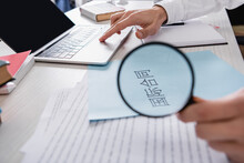 Partial View Of Interpreter Holding Magnifier Near Paper With Chinese Hieroglyphs While Working On Laptop, Blurred Foreground
