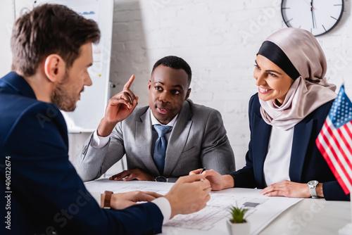 Canvas Print cheerful arabian businesswoman looking at interpreter near african american busi