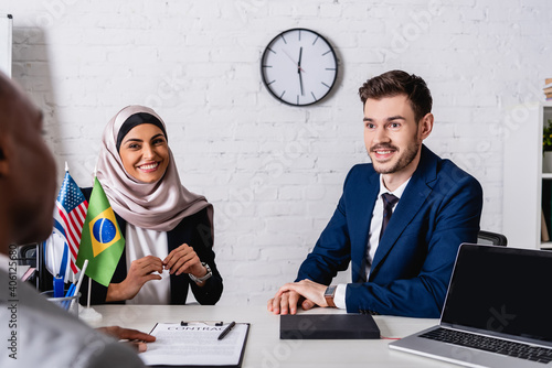 Fototapeta cheerful multicultural business partners smiling while looking to african americ