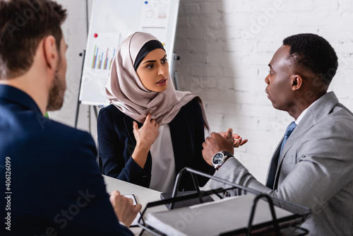 Canvas Print serious arabian businesswoman gesturing during meeting with african american bus
