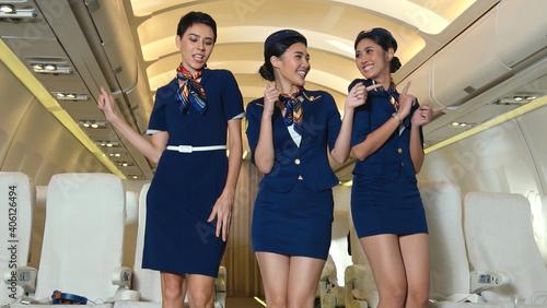 Billede på lærred Cabin crew dancing with joy in airplane